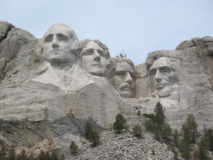 Mount Rushmore with several workers on Roosevelt's head.